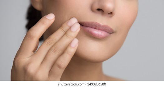 Lips Care. Woman Applying Balsam Over Grey Studio Background, Crop