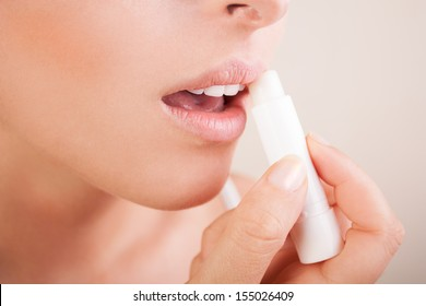 Lips care.woman applying balsam on lips.