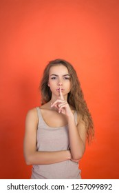 Lips and hand of beautiful young girl doing silence sign tss gesture isolated on red background with copyspace