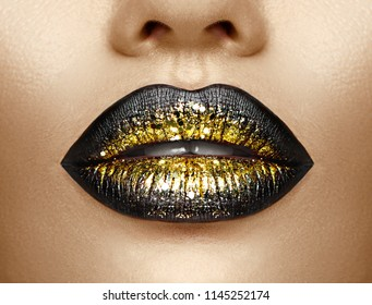Lips make-up. Beauty high fashion trendy black with gold colour gradient lips makeup sample, sexy mouth closeup. Lipstick. Professional Make up artist work