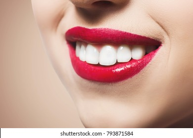 Lips makeup closeup. Red bright lipstick. Closeup of female model face with fashion glossy make-up, beauty concept
