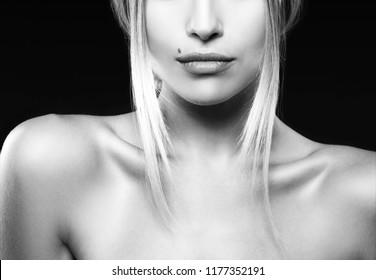 Lips, part of face and shoulders of attractive beauty model girl with clean fresh bright skin, natural nude make-up. Black background. Skincare facial treatment concept. Black and white