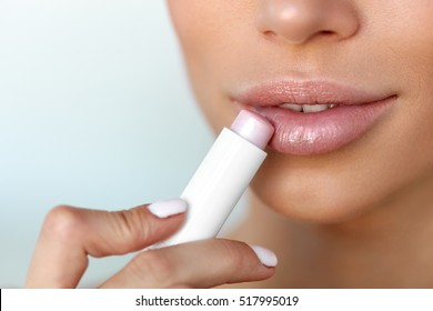 Lips Skin Care. Beautiful Woman Face With Sexy Full Lips Applying Hygienic Lip Balm, Lipcare Stick. Closeup Of Female Face With Soft Skin Putting Lip Protector Lipstick On. Beauty Cosmetics Concept