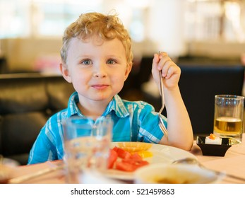 Lips smiling blond kid in plaid blue shirt is having fruit breakfast in the resort cafe