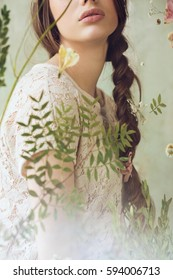 Lips of woman in lace top behind the window with flowers on it