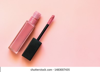Lipstick and applicator wand on pastel pink backgrpund. Liquid lip stick open tube. Makeup cosmetic product. Top view, flat lay, copy space