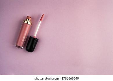 Lipstick and applicator wand on pastel pink backgrpund. Liquid lip stick open tube.