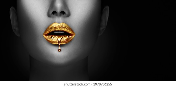 Lipstick dripping. Paint drips, lipgloss dripping from sexy lips, liquid Gold metallic paint drops on beautiful model girl's mouth, creative make-up. Desaturated Beauty woman face makeup close up. Art
