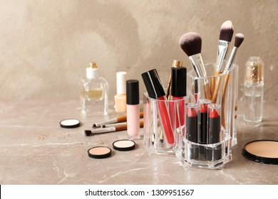 Lipstick holder with different makeup products on table against color background. Space for text