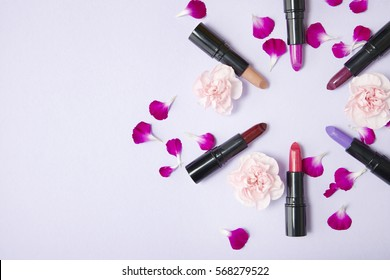 Lipstick make up and flowers arranged in a circle on a pastel purple background with blank space at side