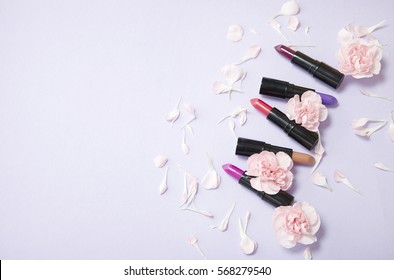 Lipstick make up and flowers arranged on a pastel purple background with empty space at side