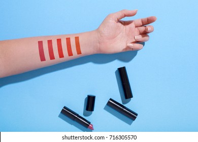 Lipstick makeup swatches on female hand, flat lay