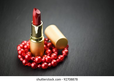 lipstick and red  jewelry on black with copy space
