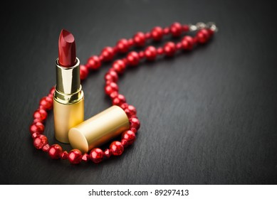 lipstick and red  necklace on black stone