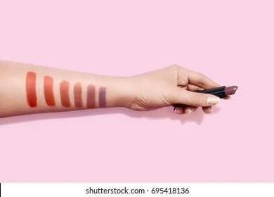 Lipstick swatches on woman hand holding lipstick