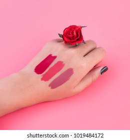 Lipstick swatches on women hand on pink background