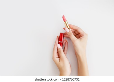 Lipstick in woman's hands on white background. Make up. Open space.