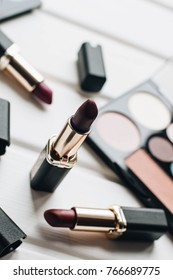 Lipsticks of different colors and eyeshadows on wooden background
