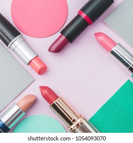Lipsticks of different colors on multicolored paper background.