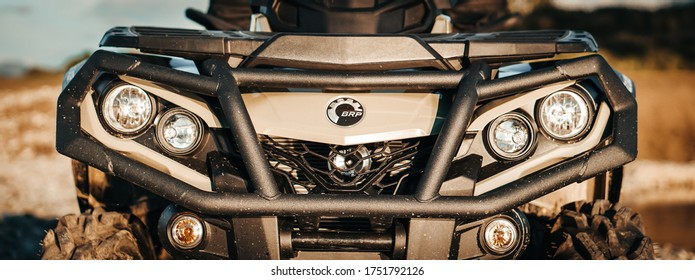 LIPTOVSKY MIKULAS, SLOVAKIA JUN 07, 2020 : Banner detail close up of army green can-am outlander atv quad motorcycle bike's front light. It look's like very aggressive and strong off - road vehicle.