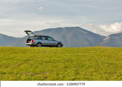 LIPTOVSKY TRNOVEC, SLOVAKIA - SEPTEMBER 30, 2017: Volkswagen hatchback car with open trunk on the top of the summer hill. Blue sky and mountains in the background.