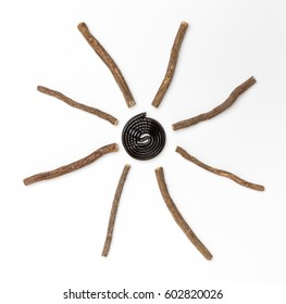 Liqorice roots and black wheel on white background. Top view.