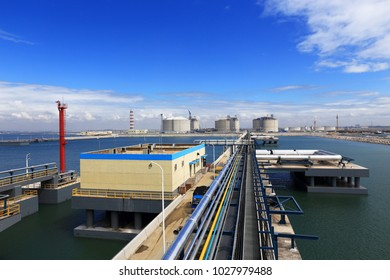 Liquefied natural gas LNG receiving station terminal unloading arm pipe storage tank blue sky and white clouds atmosphere image