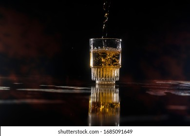 A liqueur falling down into a cup with some red smoke at night
