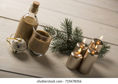 liqueur in glass with Christmas decorations on wooden background