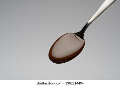 Liquid chocolate on a spoon on light grey backgiund