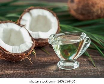 Flüssige Kokosnuss-MCT-Öl und halbierte Kokosnuss auf Holztisch. Die gesundheitlichen Vorteile von MCT-Öl. MCT oder mittelkettige Triglyceride, gesättigte Fettsäure.