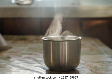 Liquid evaporation. Thermos cup with a hot drink on a cold morning. Smoke and steam.