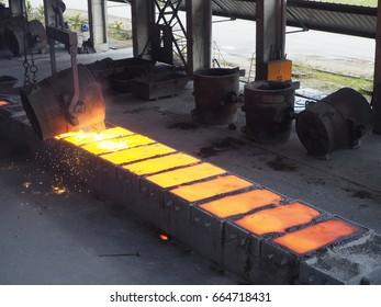 Liquid Ferro-silicon pouring from ladle into hot ingot