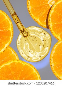 Liquid gel or serum vitamin c and oranges on a screen of microscope gray background