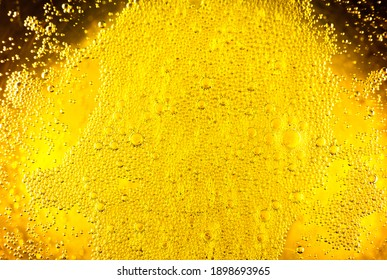 Liquid gold-yellow gasoline bubbles background on beer or champagne glass. Close up, macro shot.