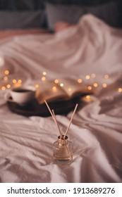 Liquid home perfume in glass bottle with sticks over glowing lights in bed at home close up. Cozy atmosphere concept. Freshness.