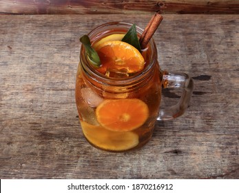 Liquid ice lemon orange tea with slice green leaf cinnamon stick in transparent glass jar mug on rustic wood background whole fruit