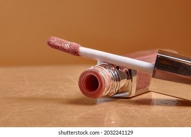 Liquid lipstick and applicator on  color background. Open tube of lip gloss and wand brush with makeup product on pastel surface. copy space