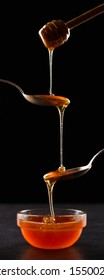 Liquid May honey flows down into spoons in a jar. Sweet cascade on black background.