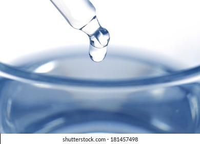 Liquid medicine in glass on white background