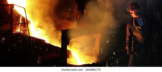Liquid metal in the foundry, melting iron in furnace, steel mill. Worker with goggles and helmet controlling iron smelting in furnaces, applying heat to ore in order to extract a base metal