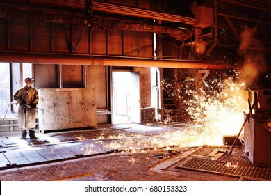 Liquid metal is poured into molds. Worker, controlling the melting of metal in furnaces. A man works at a metallurgical plant against a blast furnace