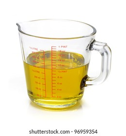 Liquid oil in measuring cup on white background