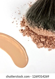 Liquid and powder makeup on white background
