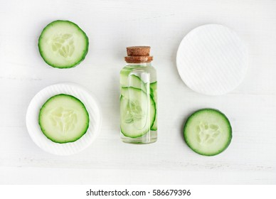 Liquid skincare cosmetic in bottle, green cucumber slice, morning facial fresh cleanser tonic, white wooden background top view