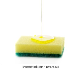 Liquid soap being poured on a dish sponge.