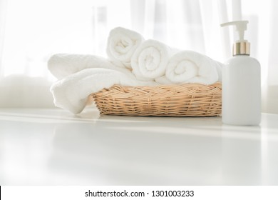 Liquid soap bottle, white towel on basket in bathroom. Hygiene and healthy life concept. Close up, selective focus