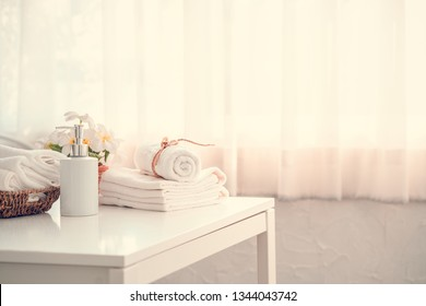 Liquid soap bottle, white towel in basket on white table. Hygiene and healthy life concept. Close up, selective focus