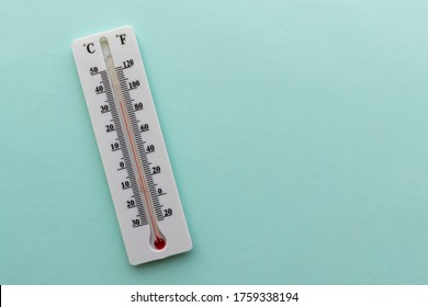 Liquid thermometer. Light green background. White plastic case, red alcohol. Two scales in degrees - celsius, fahrenheit. Temperature value is 33 C or 92 F.