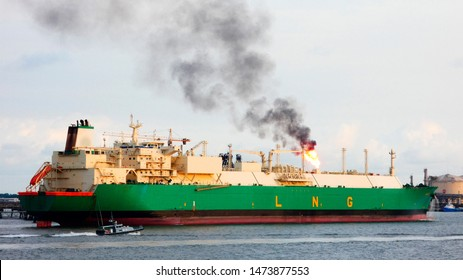 Liquified natural gas tanker loading at terminal with pollution